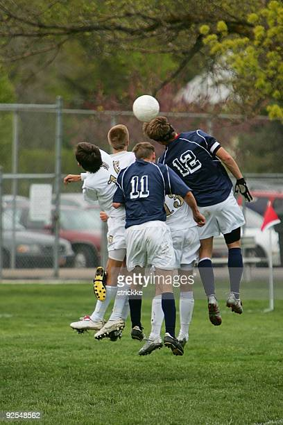 Five Young Male Soccer Players Jump to Head Ball