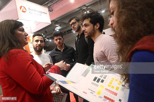 Five young people from Syria who said they all have been granted asylum in Germany learn about job training and requirements at the stand of...