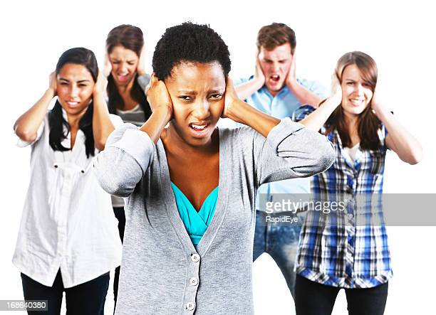 Five young people grimacing at something they hear