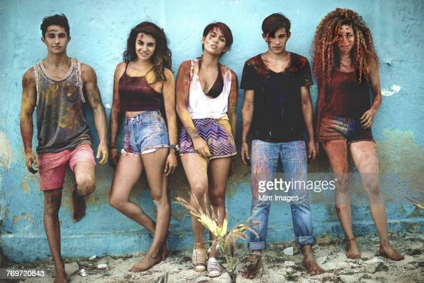Five young people lined up against a wall covered in paint looking at camera.