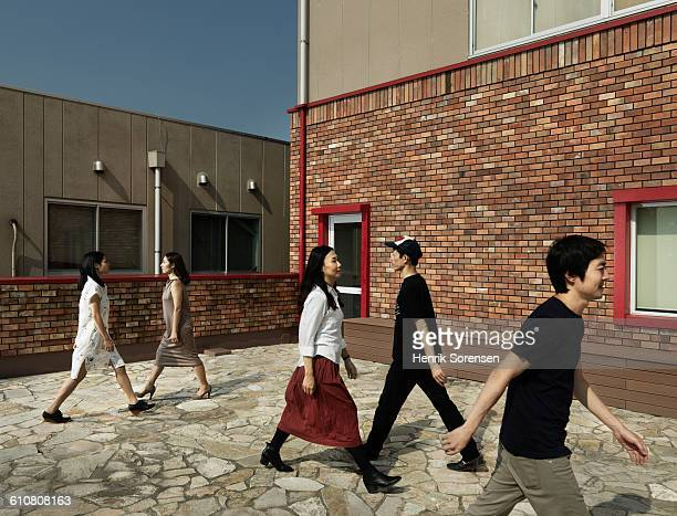 five young people passing each other