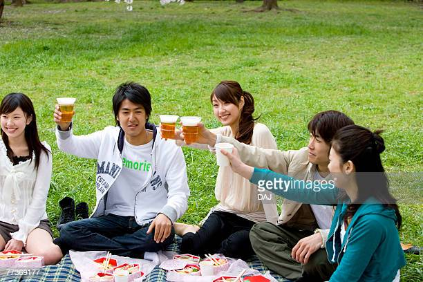 Five young people toasting with glasses, enjoying lunch on lawn, front view, side view, Japan
