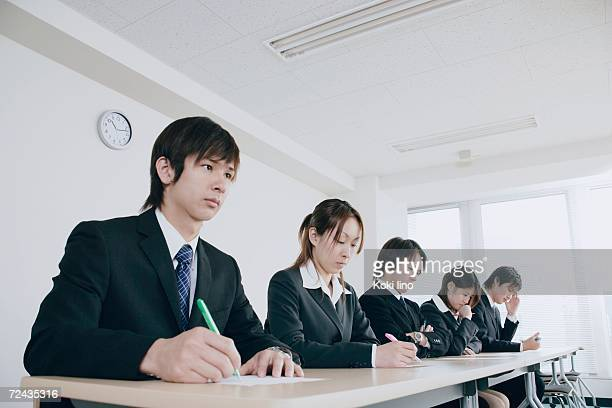 Five young people writing on exam paper