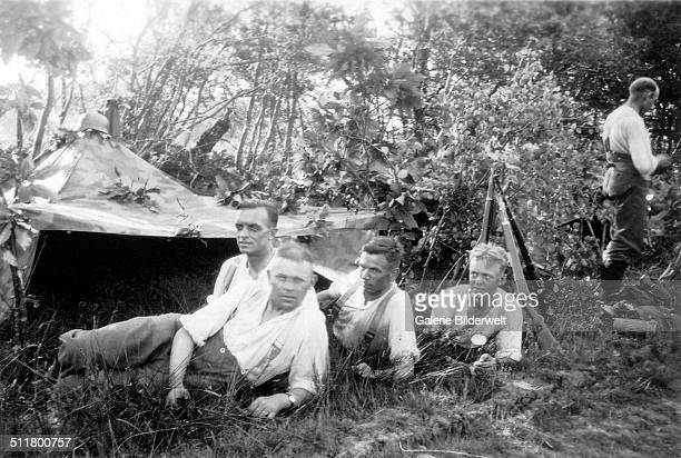 Five young soldiers of the Wehrmacht with a tent in the forest 1944 They are part of a German military encampment France