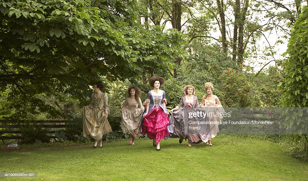 Five young women in period dresses running outside : Foto stock