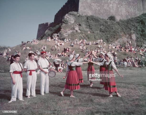 Five young women perform a Basque dance as three musicians play traditional txistu instruments during a fete in the grounds of Mont Orgueil Castle in...
