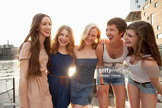 Five young women standing on a jetty next to the Spree River, Berlin, Germany