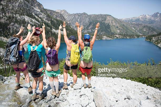 Five young women, standing on rock beside lake, arms raised, rear view, The Enchantments, Alpine Lakes Wilderness, Washington, USA