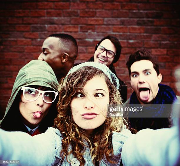 Five youngsters grimace,  taking very silly selfie
