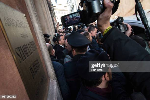 FiveStar Movement's leader Luigi Di Maio center back to the camera is mobbed by reporters as he boards a taxi as he leaves the foreign press...