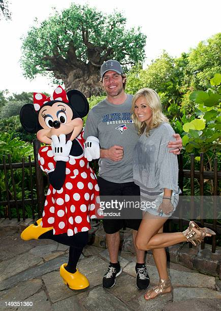 Fivetime Grammy Awardwinning singer Carrie Underwood and her husband NHL Nashville Predators star Mike Fisher pose with Minnie Mouse at Disney's...