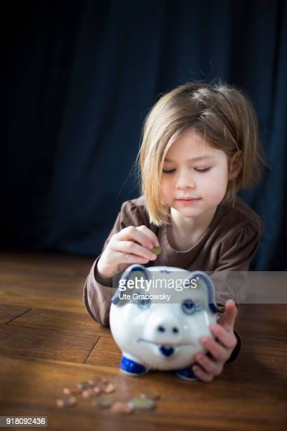 Fiveyear old girl poses with a piggy bank on February 03 2018 in Bonn Germany