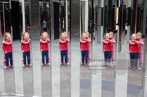 Fiveyear old twins Stella and Olivia wander through a maze of mirrored panels that create many reflections at the National Gallery of Victoria...