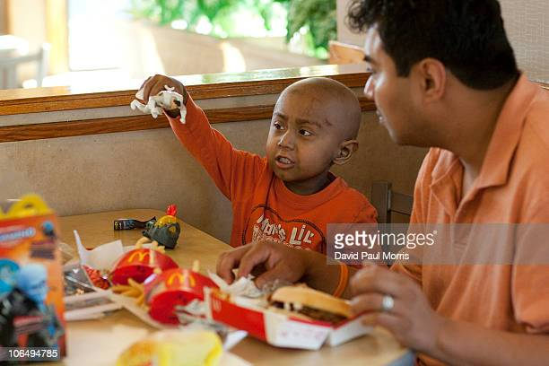 Fiveyearold Andy Villatoro plays with a toy he received after ordering a Happy Meal at McDonald's as his father Carlos Villatoro watches on November...