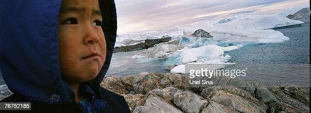 Fiveyearold Angut Rosbach looks on from an island where he came with his father Arne Lange to hunt seals August 26 2007 near Ilimanaq Greenland Lange...