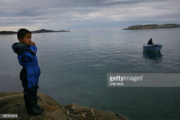 Fiveyearold Angut Rosbach waits on a cliff for his father Arne Lange to set off for seal hunting August 26 2007 near their home village of Ilimanaq...