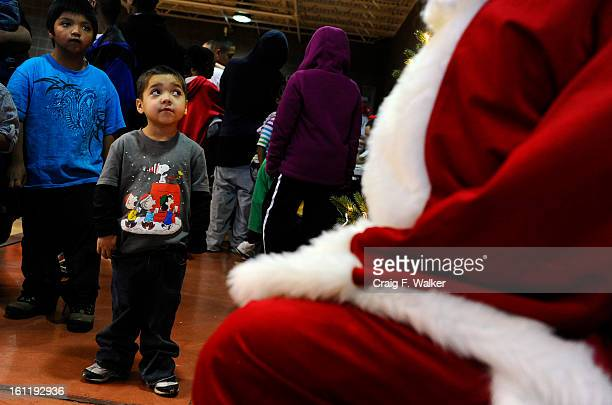 Five-year-old Dominic Montes and his brother Eduardo, left, wait to visit with Santa during Delta Eta Boule's Toys For Tots Christmas Celebration at...