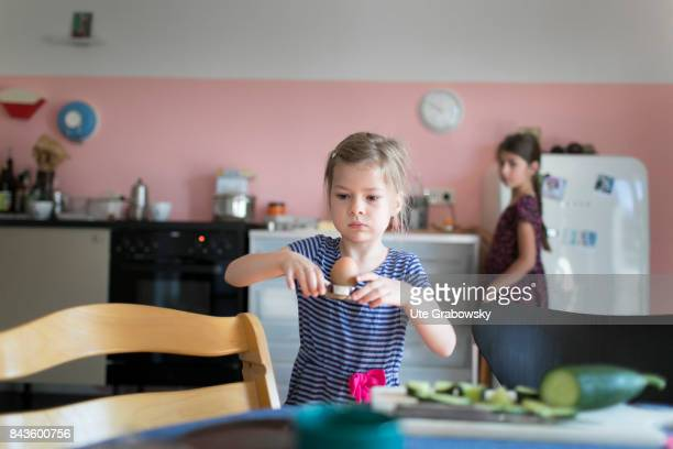 A fiveyearold girl helps to cover the breakfast table and carries a boiled egg on August 07 2017 in Bonn Germany