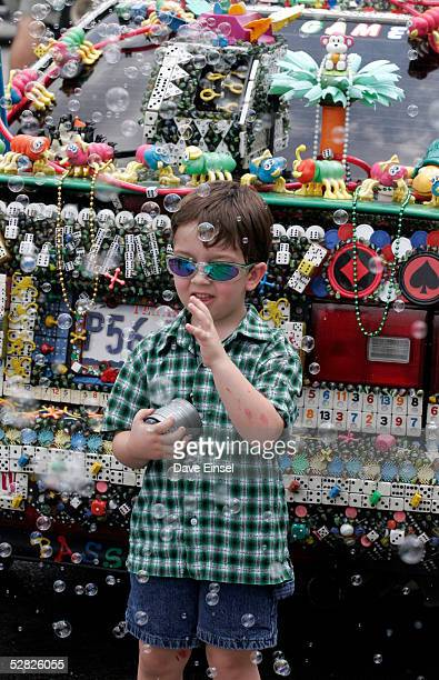 """Five-year-old Hayden Hall is surrounded by bubbles coming from """"R U Game"""" during the Everyone's Art Car Parade May 14, 2005 in Houston, Texas. The..."""