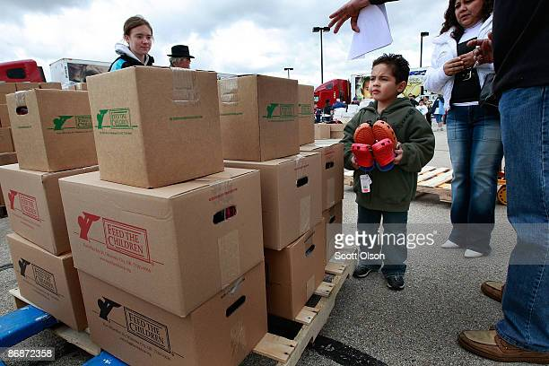 Fiveyearold Kevin Estrada walks with a palletload of relief supplies his family received at a distribution site hosted by Feed The Children on May 9...