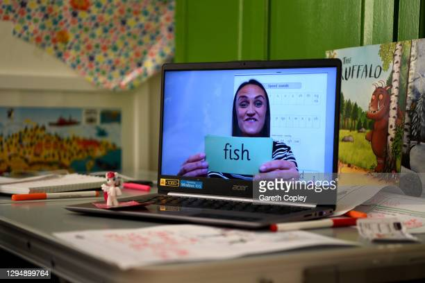 Five-year-old Lois Copley-Jones , who is the photographer's daughter, watches an online phonics lesson on a laptop in her bedroom on the second day...