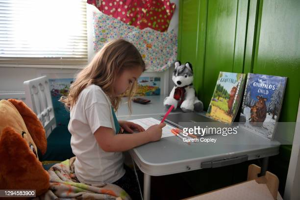 Five-year-old Lois Copley-Jones, who is the photographer's daughter, does her English work in her bedroom on the first day of the nationwide school...
