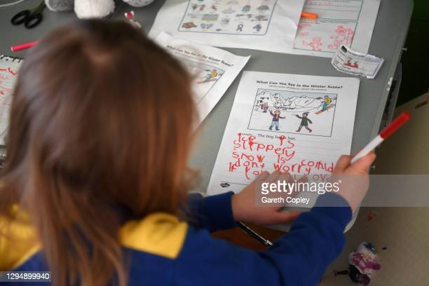 Five-year-old Lois Copley-Jones, who is the photographer's daughter, does her English studies in her bedroom on the second day of the nationwide...