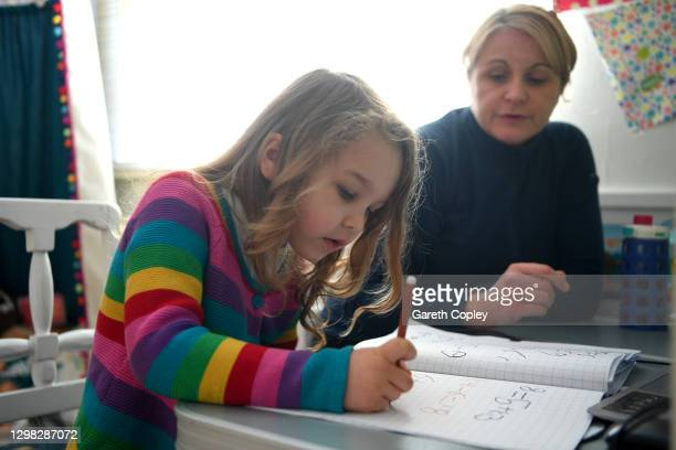 Five-year-old Lois Copley-Jones, who is the photographer's daughter, does her Maths studies in her bedroom on January 25, 2021 in...