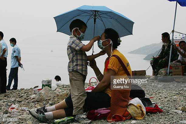 A fiveyearold son arrange his mother's mask as they arrive at a landing point at Zipingba dam from Yingxiu county on May 16 2008 in Sichuan province...