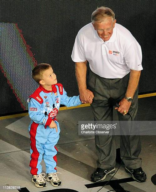 Fiveyearold Taylor Gibbs looks up at his grandfather Joe Gibbs after he gave the prayer prior to the running of the NASCAR Sprint AllStar race...