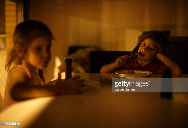 Fiveyearold twin sisters Kiomara Laguna Arias and Tatiana who were evicted from their home with their parents and brother eat their dinner lit by the...