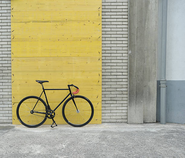 Old Bicycle parked against worn yellow wall | Photos.com