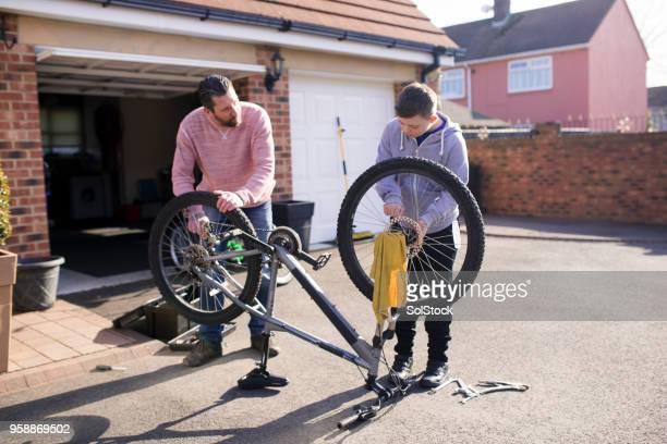 fixing a bike at home - adjusting stock photos and pictures