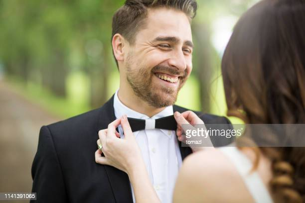fixing groom's bowtie at a wedding - adjusting stock pictures, royalty-free photos & images
