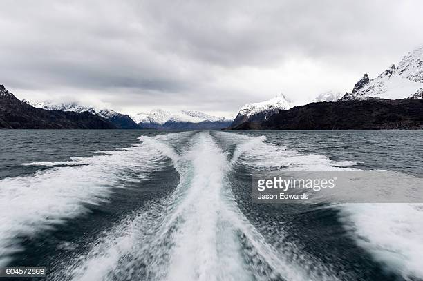 A boats wake peels between snow covered peaks in a fjord.