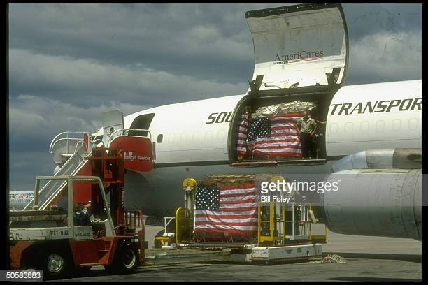 US flag adorned AmeriCares relief supplies for Iranian earthquake victims being loaded onto 707 cargo plane for transport to Iran