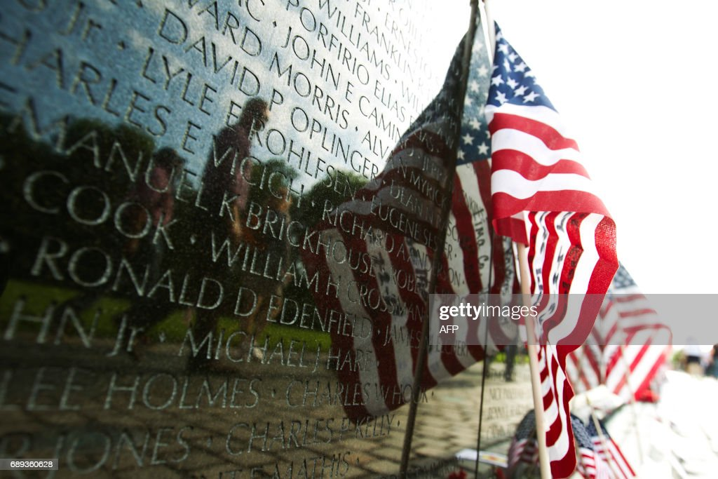 A US flag adorns the wall of the Vietnam Veterans Memorial in Washington DC, May 28, 2017. Motorcyclists are in Washington for the traditional annual Rolling Thunder ahead of Memorial Day, May 29. / AFP PHOTO / Jose Luis Magana