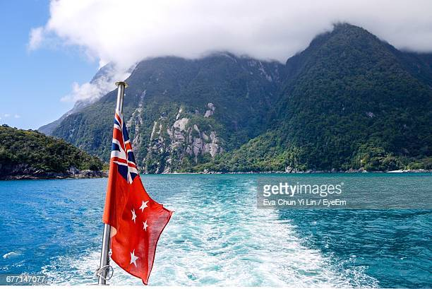 flag against mountains - new zealand flag stock photos and pictures