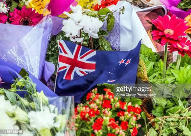 flag and flowers in support - christchurch nova zelândia - fotografias e filmes do acervo