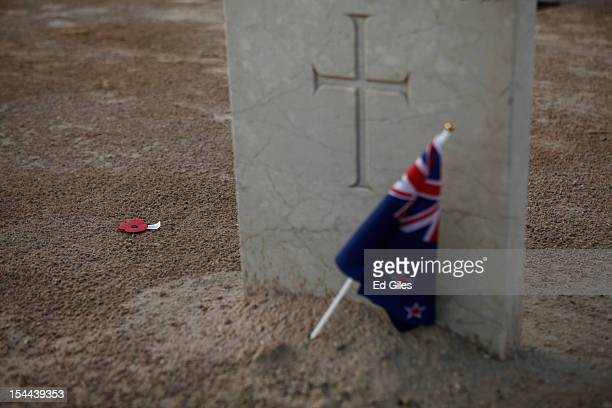 A flag and remembrance poppy lie at the grave of a Commonwealth solider of the Second World War stands at the El Alamein Commonwealth War Cemetery...
