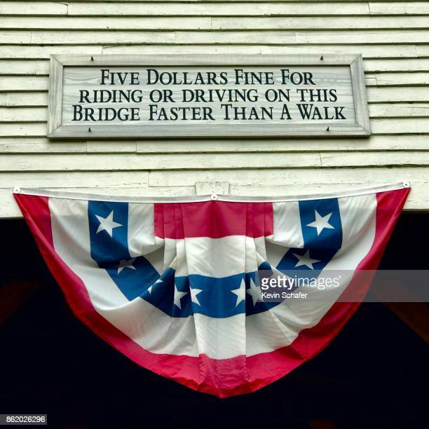 flag and sign on covered bridge , new hampshire - covered bridge stock photos and pictures