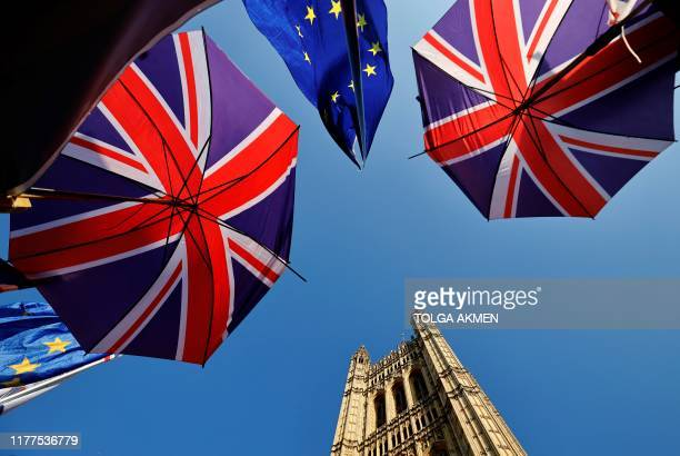 EU flag and Union flagthemed umbrellas of Brexit activists fly outside the Houses of Parliament in London on October 22 as MPs begin debating the...