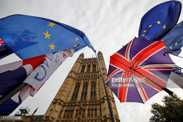 EU flag and Union flagthemed umbrellas of Brexit activists fly outside the Houses of Parliament in London on October 23 2019 British Prime Minister...