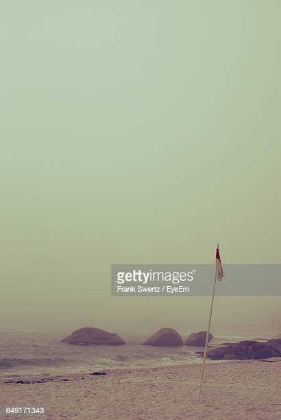 flag at sea shore against clear sky - frank swertz stock photos and pictures