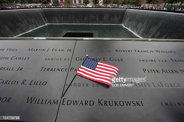 A US flag at the memorial wall on the South Tower reflecting pool of the World Trade Center September 11 2011 in New York AFP PHOTO/DON EMMERT