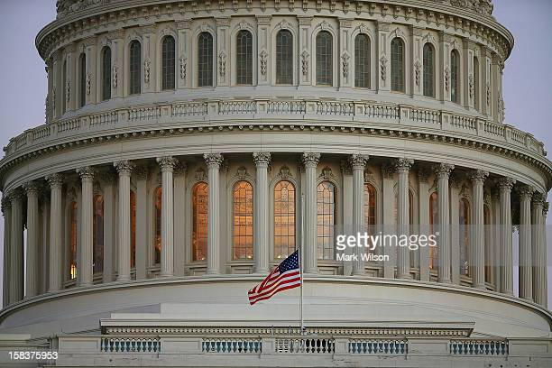 A flag at the US Capitol flies at half staff after President Barack Obama ordered the action while speaking on the shootings at the Sandy Hook...