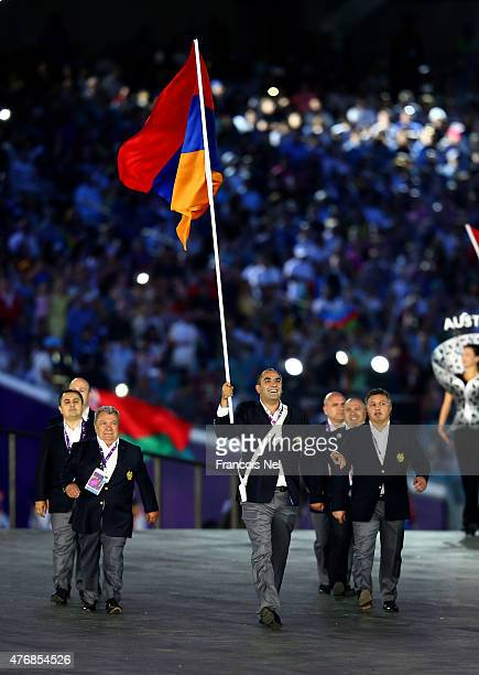 flag bearer and Secretary General of the Armenian Olympic Committee Hrachya Rostomyan of Armenia leads his team into the stadium during the Opening...