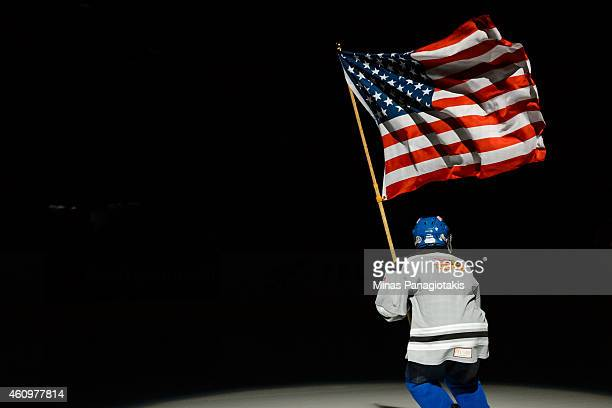 A flag bearer carries the United States flag during the 2015 IIHF World Junior Hockey Championship game between Team Germany and Team United States...