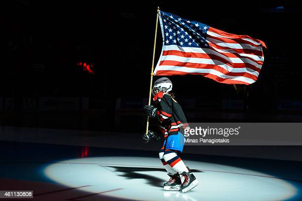 A flag bearer carries the United States flag in a quarterfinal round during the 2015 IIHF World Junior Hockey Championships between Team Russia and...