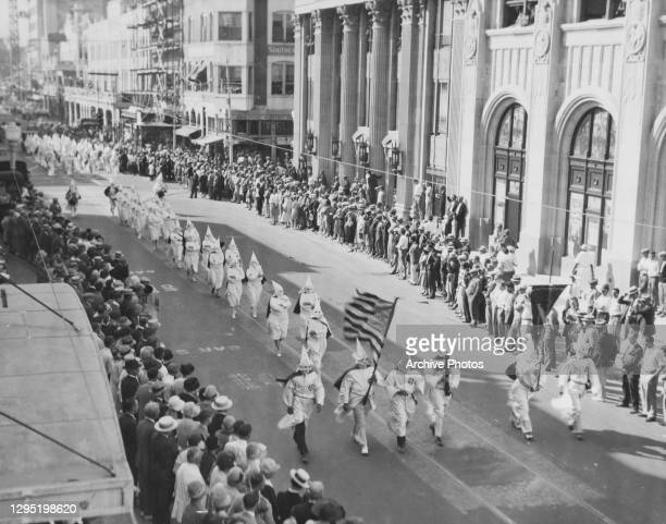 Flag bearer, carrying the Stars-and-Stripes, as they lead a Ku Klux Klan procession through a city centre, watched by crowds on either side of the...